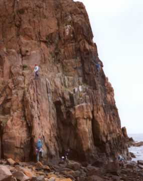 [View of climbers on The Hawkcraig sea cliff]